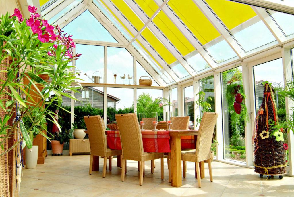 Veranda Markilux arredata con tende da sole sedie tavolo fiori